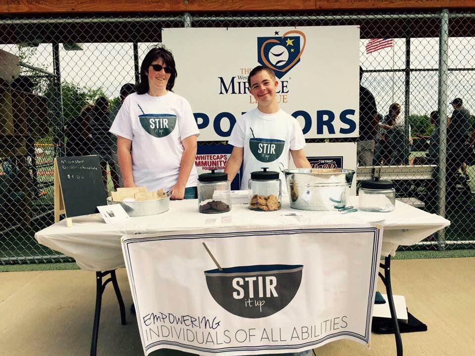Jessie and Kyle, employees of Stir It Up bakery, sell baked goods at West Michigan Miracle League